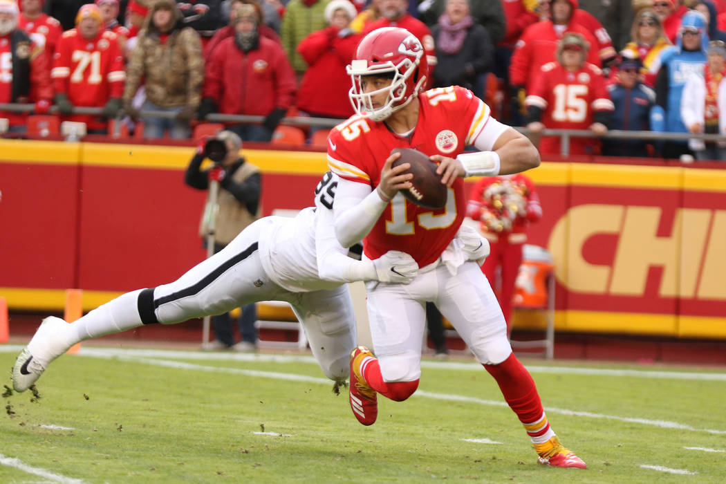 Kansas City Chiefs quarterback Patrick Mahomes (15) sheds a tackle by Oakland Raiders defensive ...