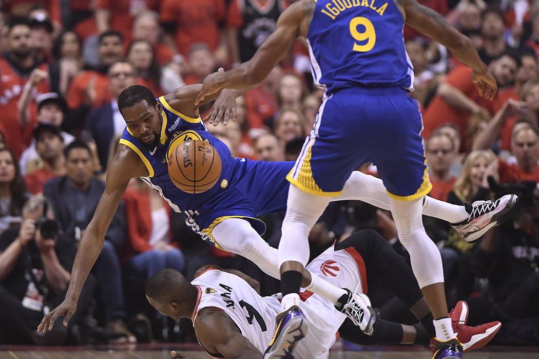 Golden State Warriors forward Kevin Durant, left, falls over Toronto Raptors center Serge Ibaka ...