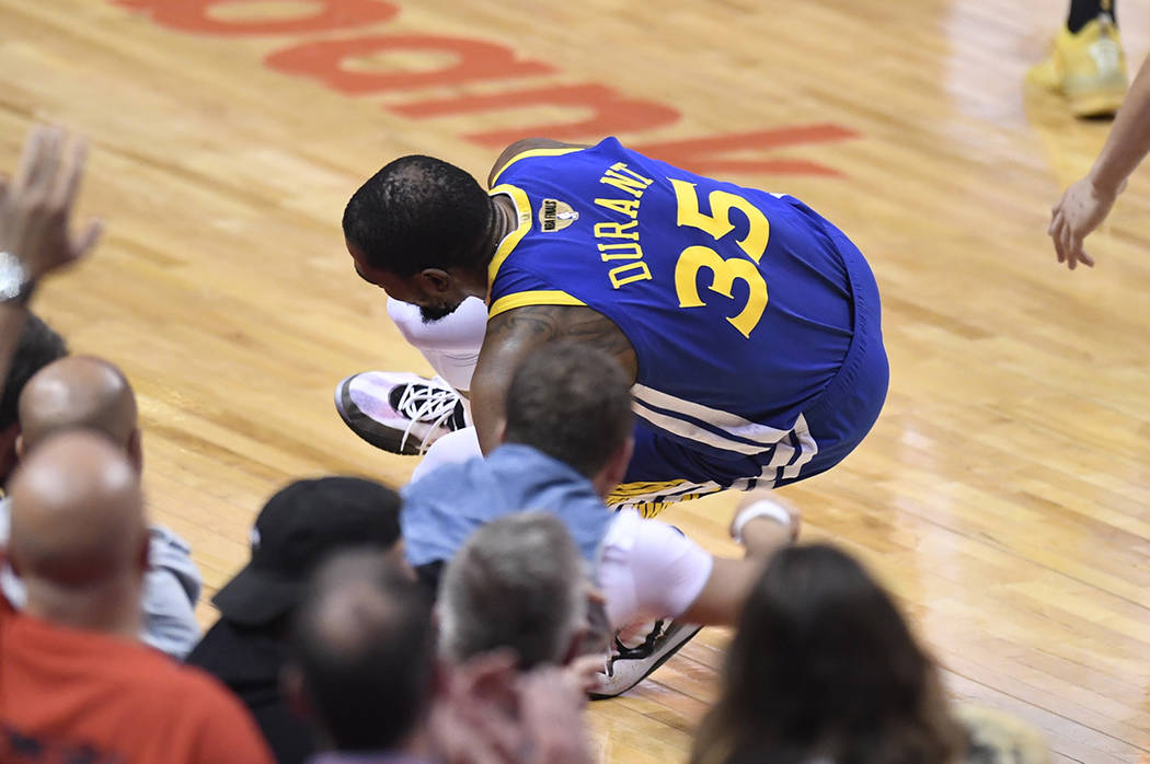 Golden State Warriors forward Kevin Durant (35) goes down with a leg injury against the Toronto ...