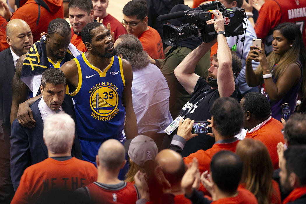 Golden State Warriors forward Kevin Durant glances up at the stands as he walks off the court a ...