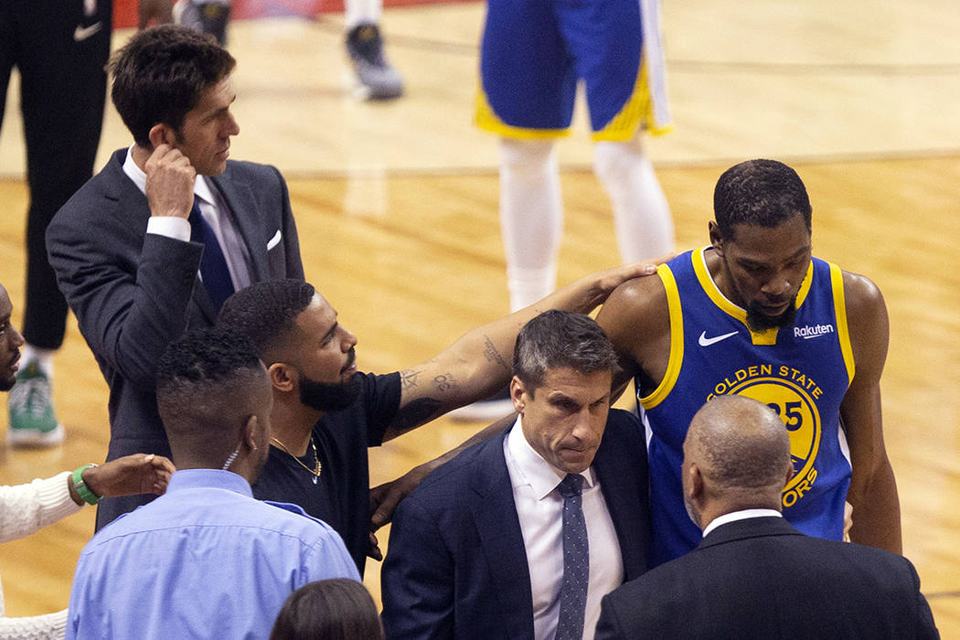 Golden State Warriors forward Kevin Durant, right, is consoled by Drake as he walks off the cou ...