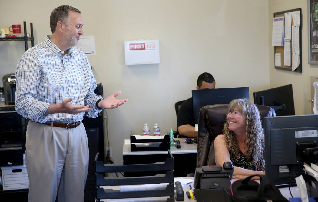 Paul Truman, owner of Truline Corporation, talks to Pam Mrgan, fleet manager, at his trucking c ...