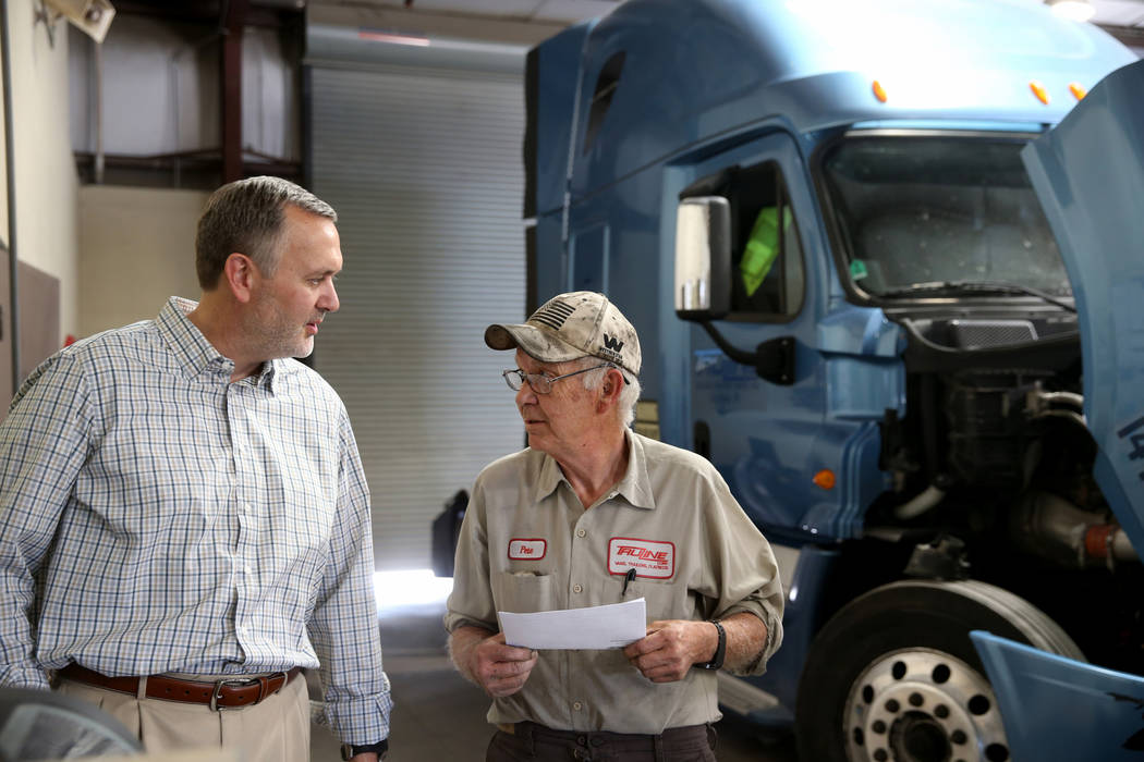 Paul Truman, owner of Truline Corporation, talks to mechanic Pete Schladweiler at his trucking ...