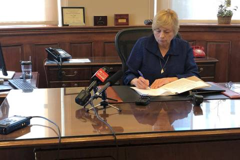 Maine Democratic Gov. Janet Mills signs a bill Wednesday, June 12, 2019, in her office in Augus ...