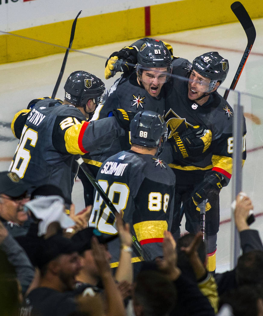"""Golden Knights players celebrate the """"hat trick"""" by their right wing Mark Stone (61) ..."""