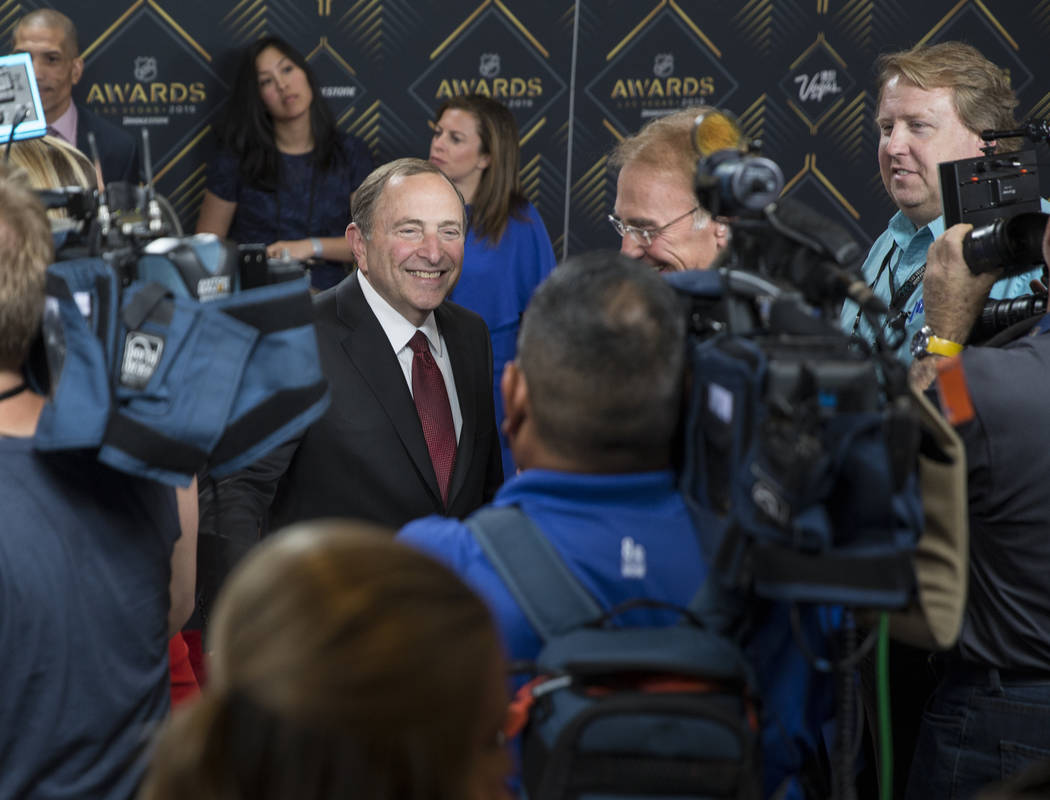 NHL commissioner Gary Bettman, left, talks with media on the red carpet before the start of the ...