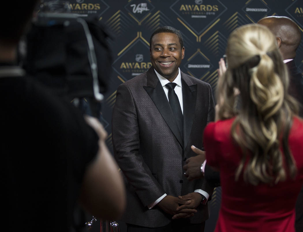 NHL Awards host Kenan Thompson, middle, talks with media on the red carpet before the start of ...