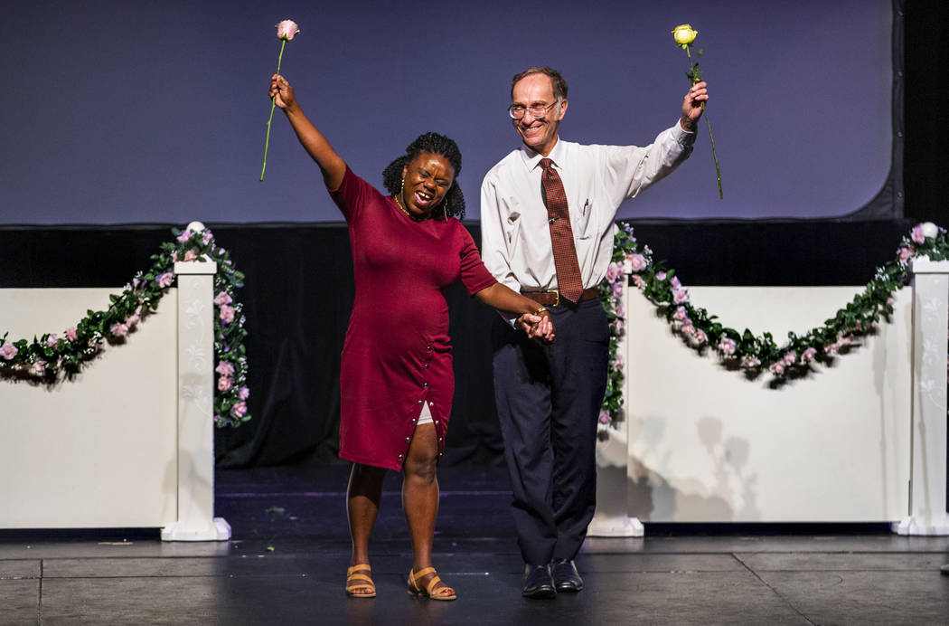 Sherene Facey and William Archbold hold hands with roses aloft during a Bridge of Peace Reconci ...