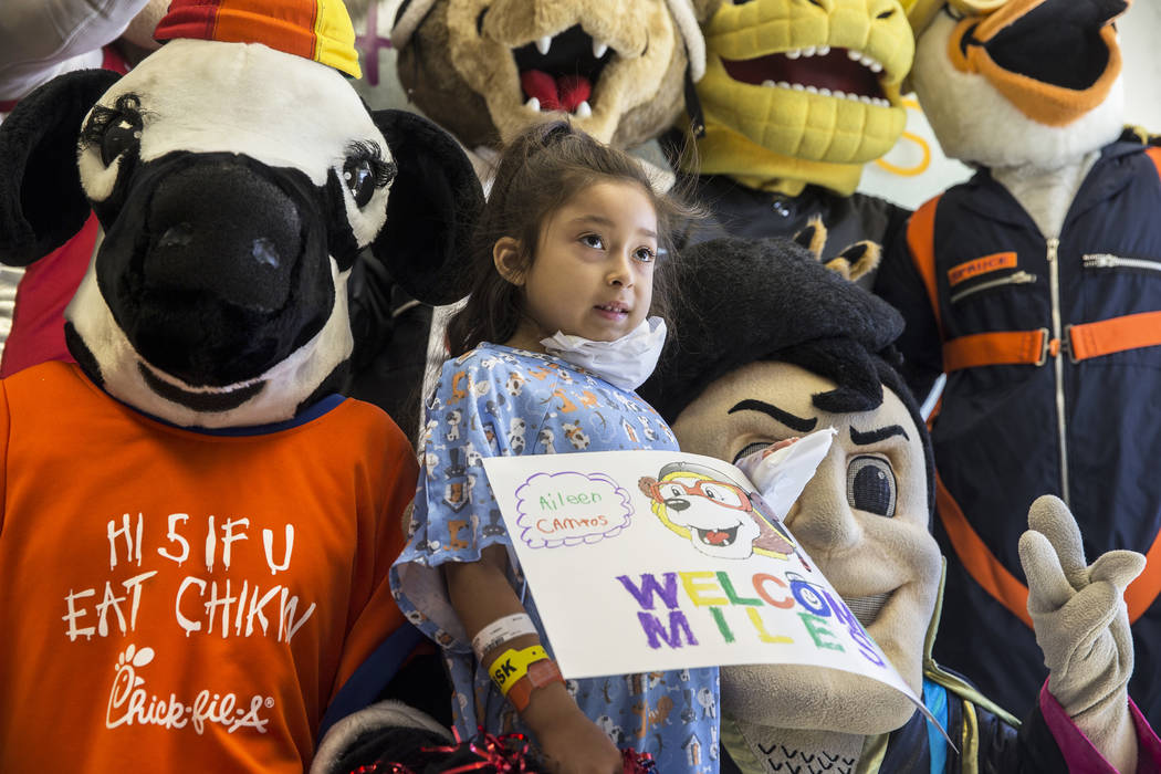 Zaryah Robbs, second from left, 8, takes a photo with the Chick-fil-A Cow, left, and the LV Lig ...