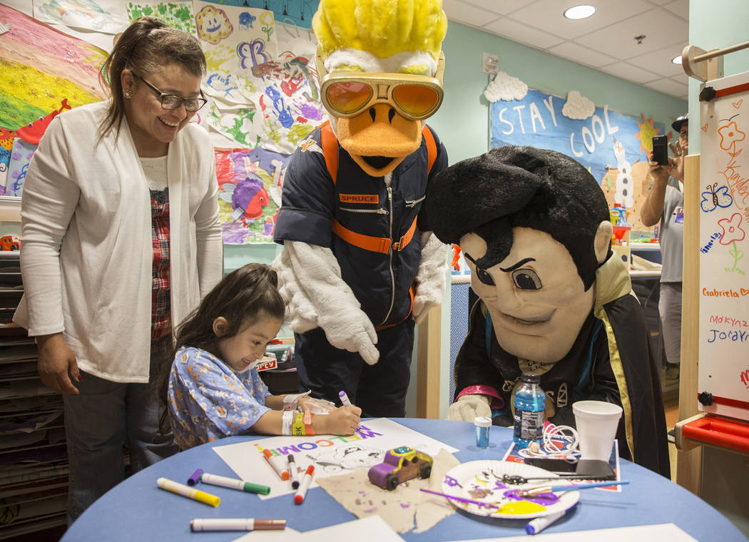 Nilda Campos, left, helps her granddaughter Zaryah Robbs, 8, draw a picture with Aviator mascot ...