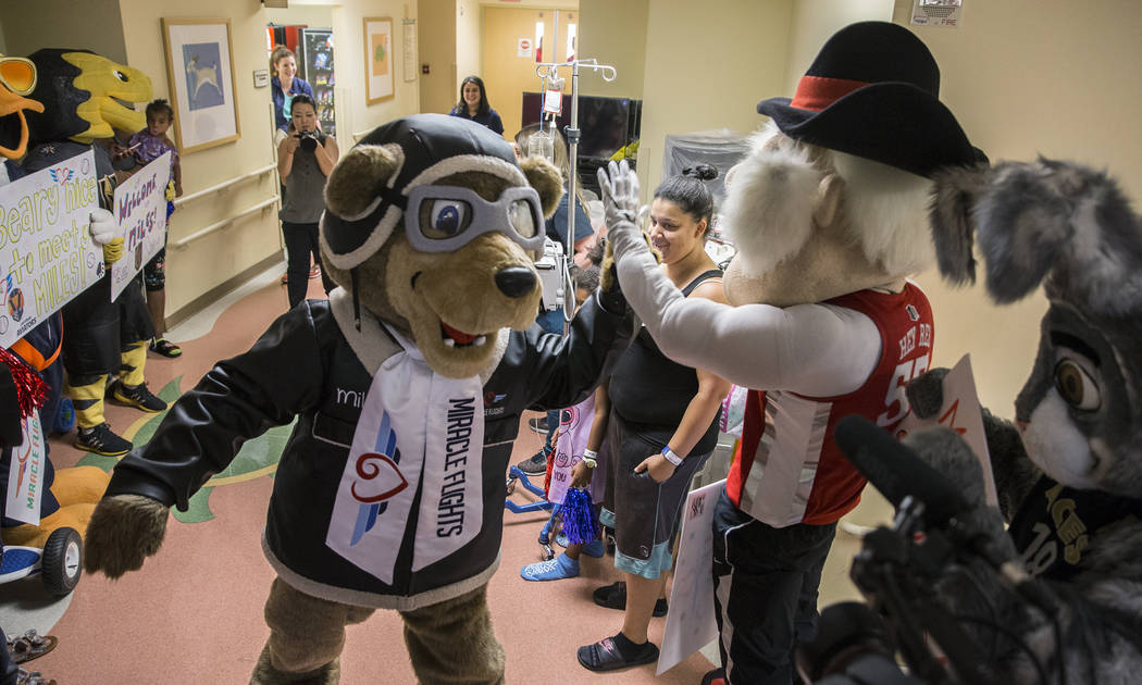 Miles the Miracle Flights Bear, the new mascot for Miracle Flights, greets UNLV's Hey Reb! duri ...
