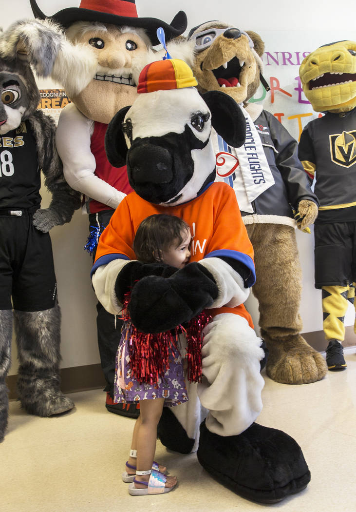 Camila Silva, 2, hugs the Chick-fil-A Cow during a welcome event for Miles the Miracle Flights ...