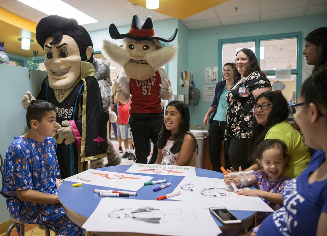 Joshua Gallardo, left, 11, Jazlin Martinez, 11, and Camila Silva, 2, are greeted by LV Lights F ...