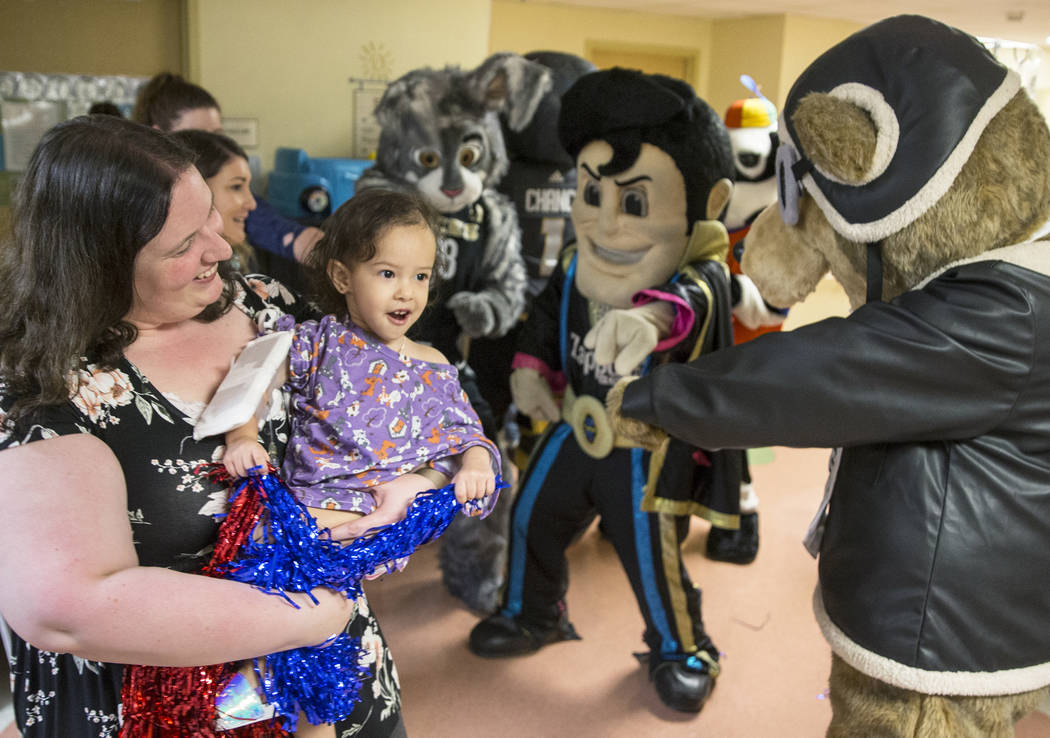 Krystle Hunter, left, holds Camila Silva, 2, as they dance with a group of Las Vegas-based masc ...