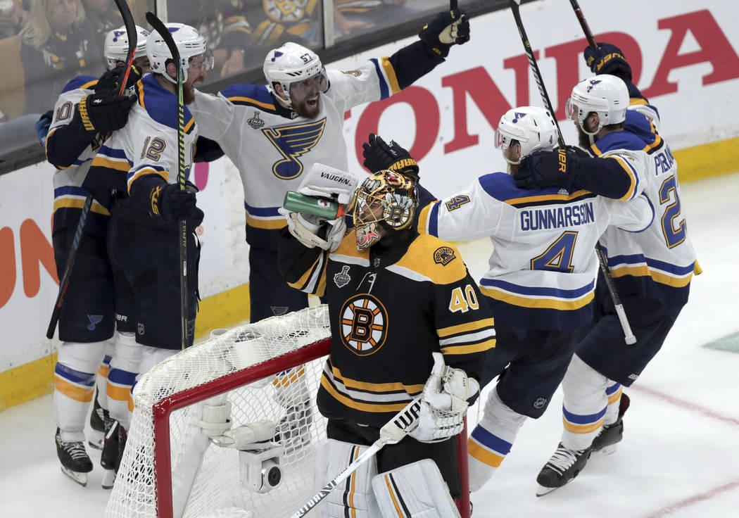 St. Louis Blues' Zach Sanford (12) celebrates his goal with teammates behind Boston Bruins goal ...