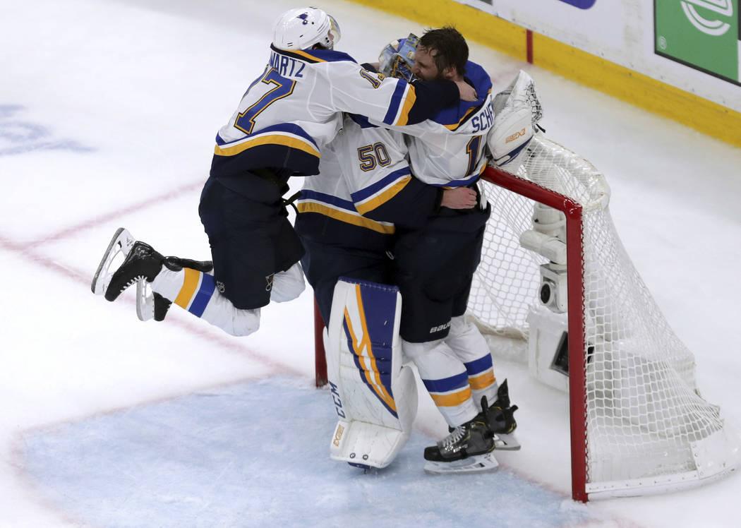 St. Louis Blues' Jaden Schwartz, left, and Brayden Schenn, right, mob goaltender Jordan Binning ...