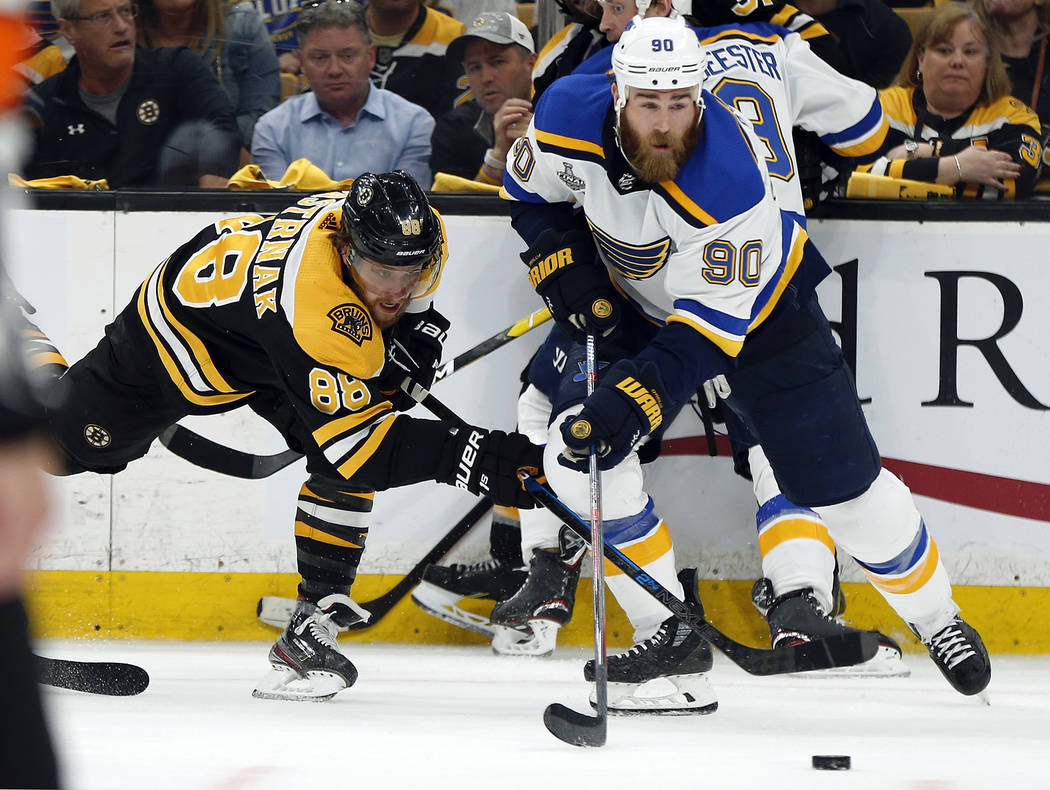 St. Louis Blues' Ryan O'Reilly (90) moves the puck away from Boston Bruins' David Pastrnak, lef ...
