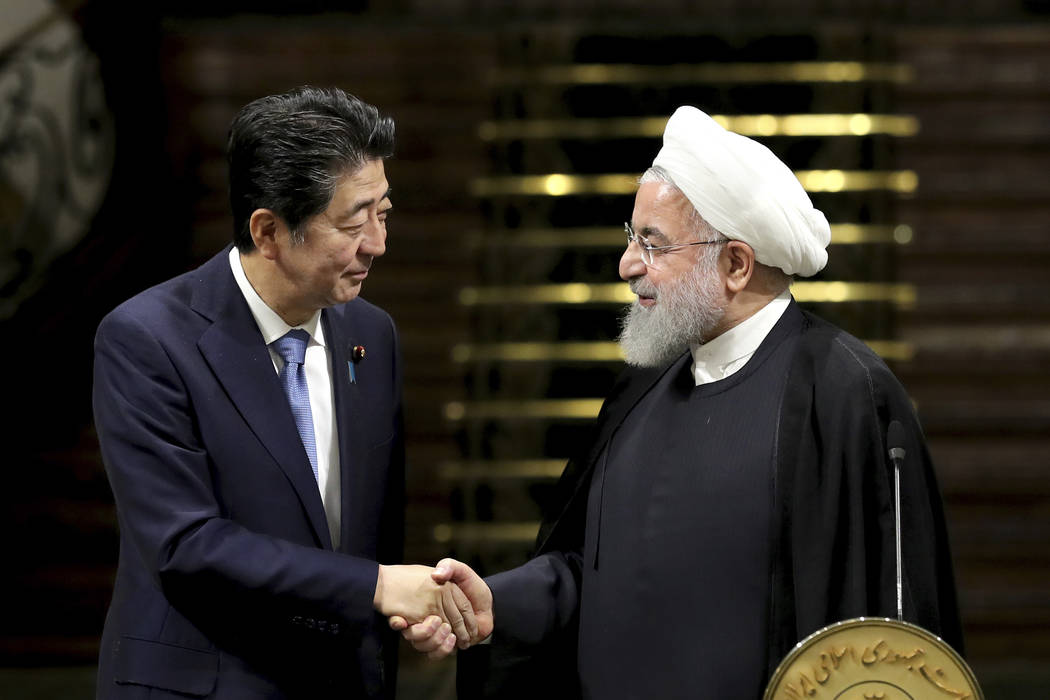 Japanese Prime Minister Shinzo Abe, left, and Iranian President Hassan Rouhani shake hands afte ...