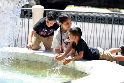 Children cool themselves at The Venetian water fountain on the Las Vegas Strip. Tempe ...