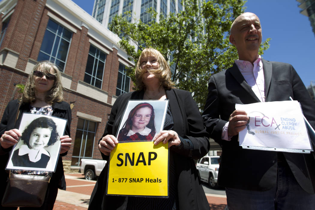Becky Ianni, center, a victim of priest abuse, holds a picture of her younger self along with o ...