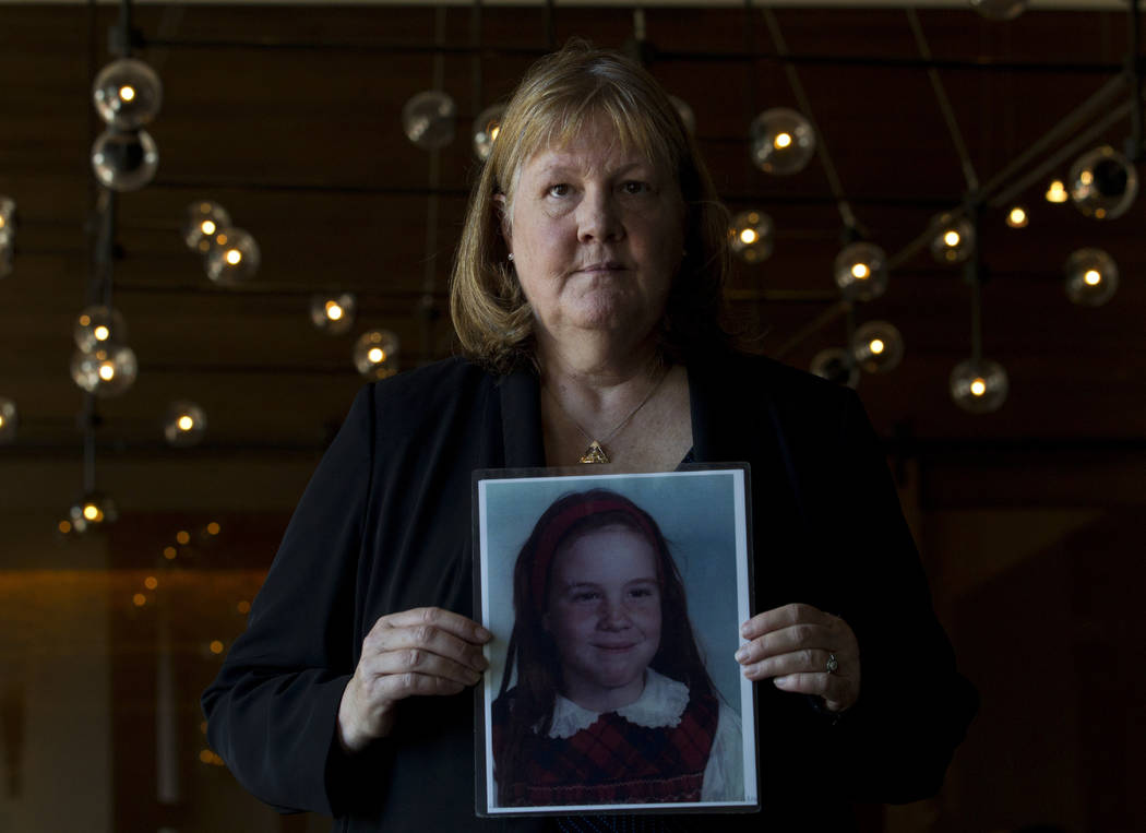 Becky Ianni, a victim of priest abuse, poses for a portrait with a picture of her younger self, ...