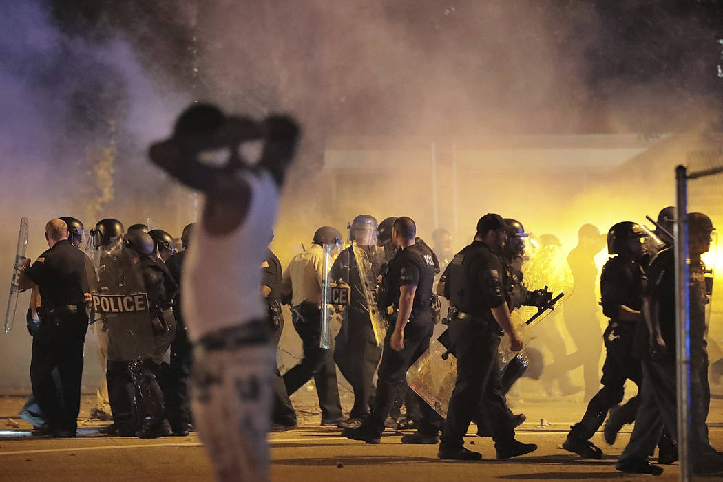 Police retreat under a cloud of tear gas as protesters disperse from the scene of a standoff af ...