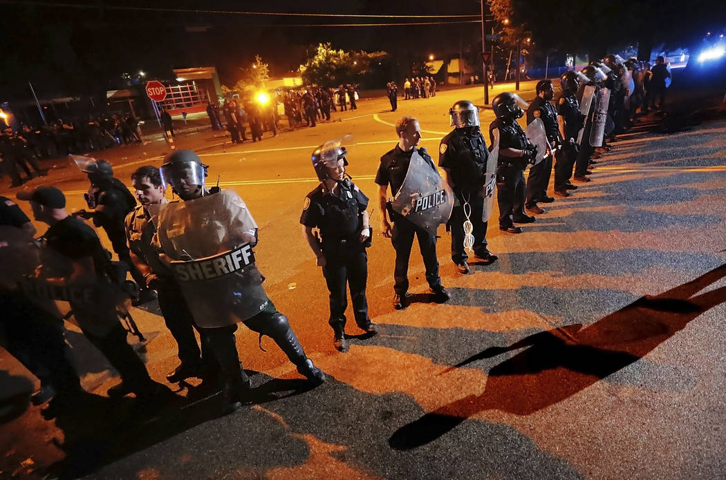 Authorities maintain a perimeter around the crime scene after protesters took to the streets of ...