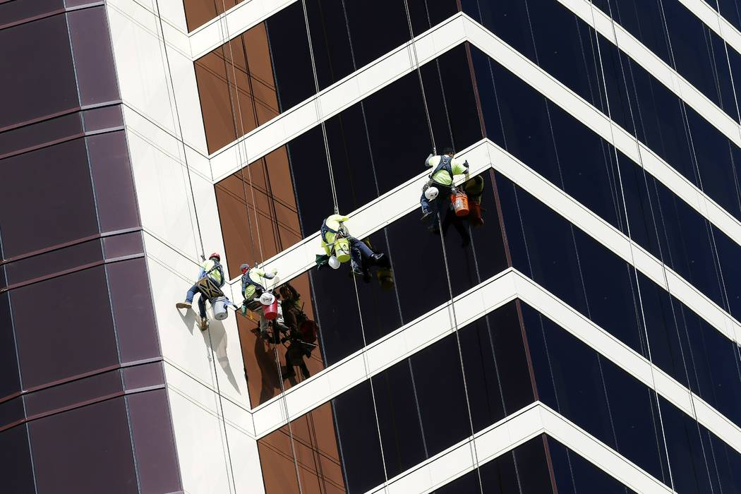 Window washers work on Encore Boston Harbor in Everett, Mass., Wednesday, May 22, 2019. MGM Res ...