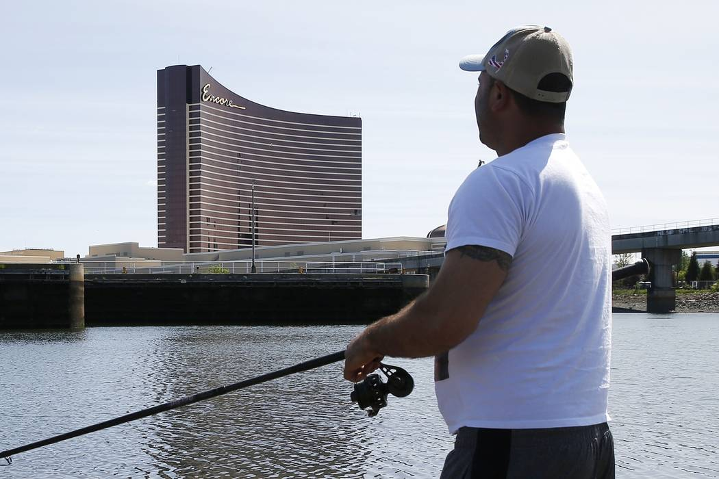 A man fishes in the Mystic River in Somerville, Mass., across from Encore Boston Harbor, Wednes ...