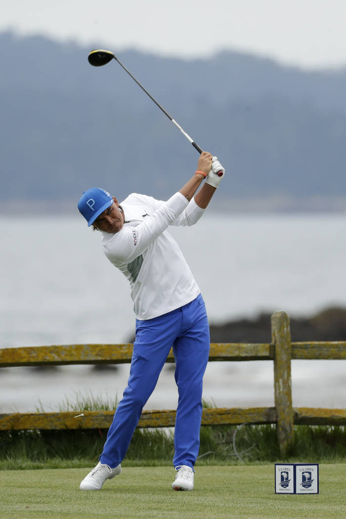 Rickie Fowler watches his tee shot on the 18th hole during the first round of the U.S. Open Cha ...