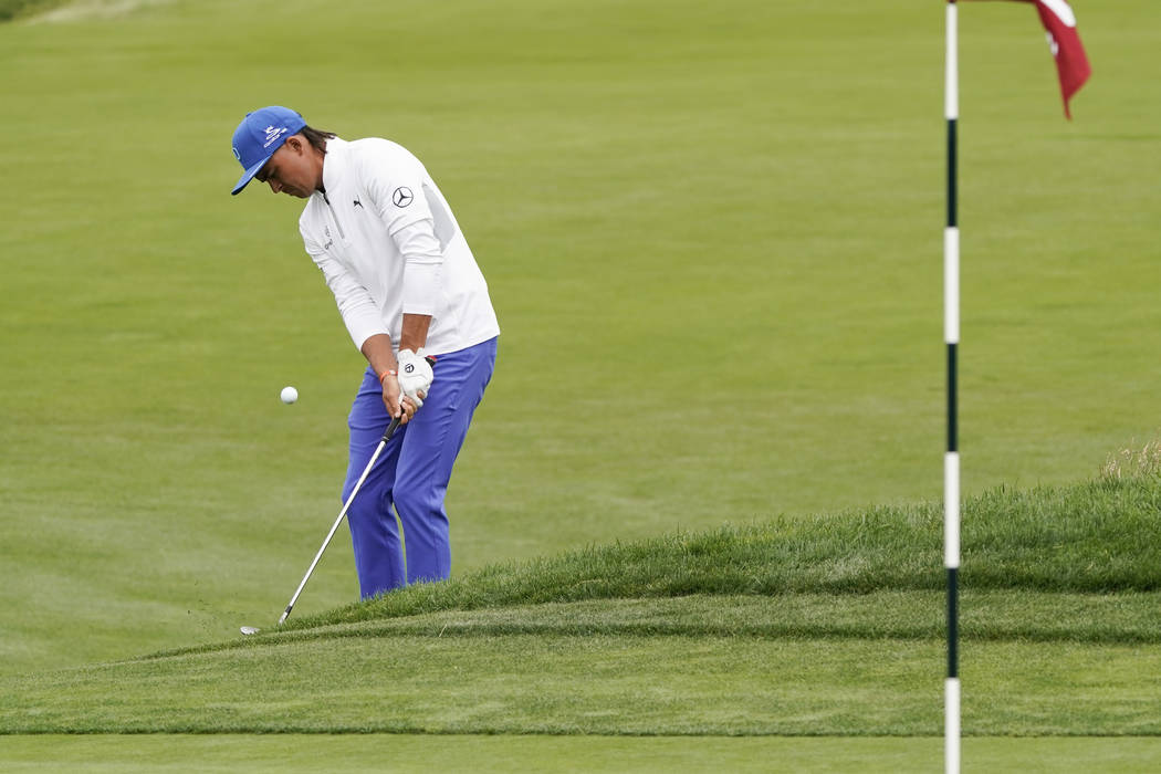 Rickie Fowler hits a chip shot on the ninth hole during the first round of the U.S. Open Champi ...