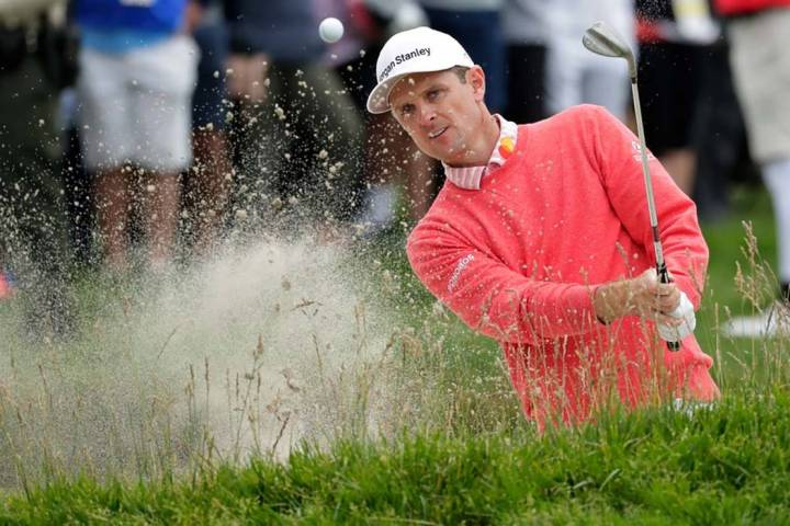 Justin Rose, of England, hits out of the bunker on the 15th hole during the first round of the ...