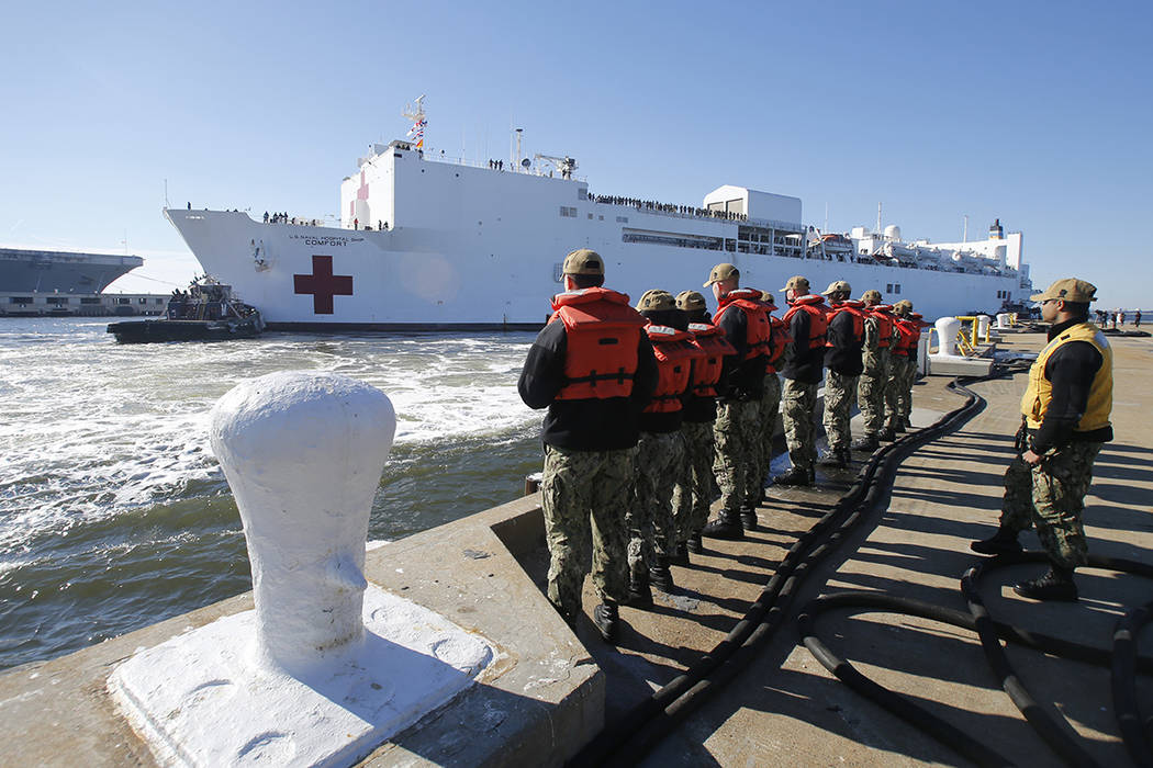 FILE - In this Dec. 18, 2018 file photo, line handlers wait as the US Navy Hospital Ship USNS C ...