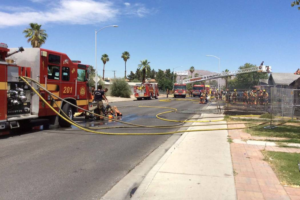Las Vegas firefighters work a fire that started in one house and spread to two others in the 21 ...