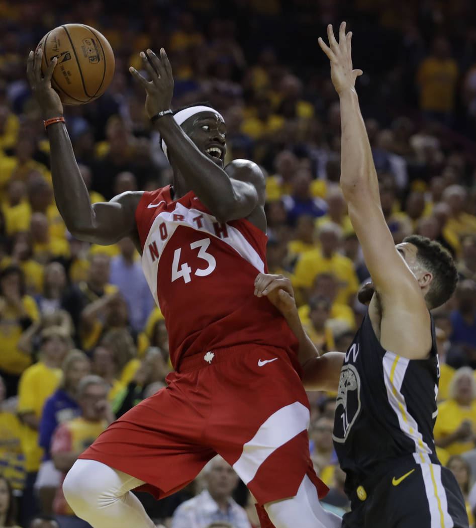 Toronto Raptors' Pascal Siakam, left, looks to pass away from Golden State Warriors' Klay Thomp ...