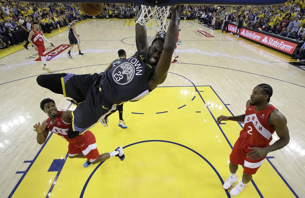 Golden State Warriors forward Draymond Green (23) dunks over Toronto Raptors guard Kyle Lowry, ...