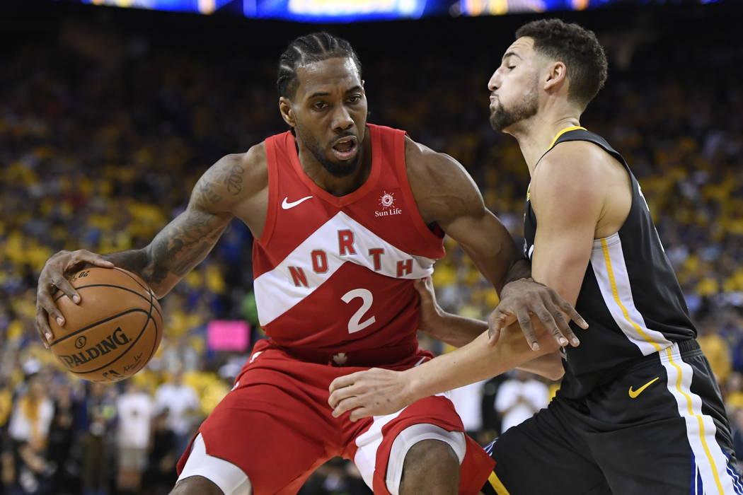 Toronto Raptors forward Kawhi Leonard (2) handles the ball while Golden State Warriors guard Kl ...