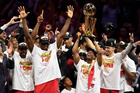 Toronto Raptors guard Kyle Lowry, center right, holds Larry O'Brien NBA Championship Trophy aft ...