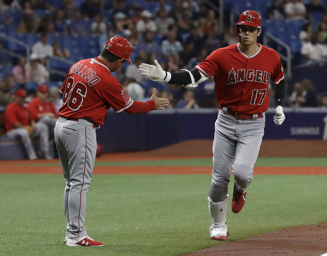 Los Angeles Angels' Shohei Ohtani (17), of Japan, shakes hands with third base coach Mike Galle ...