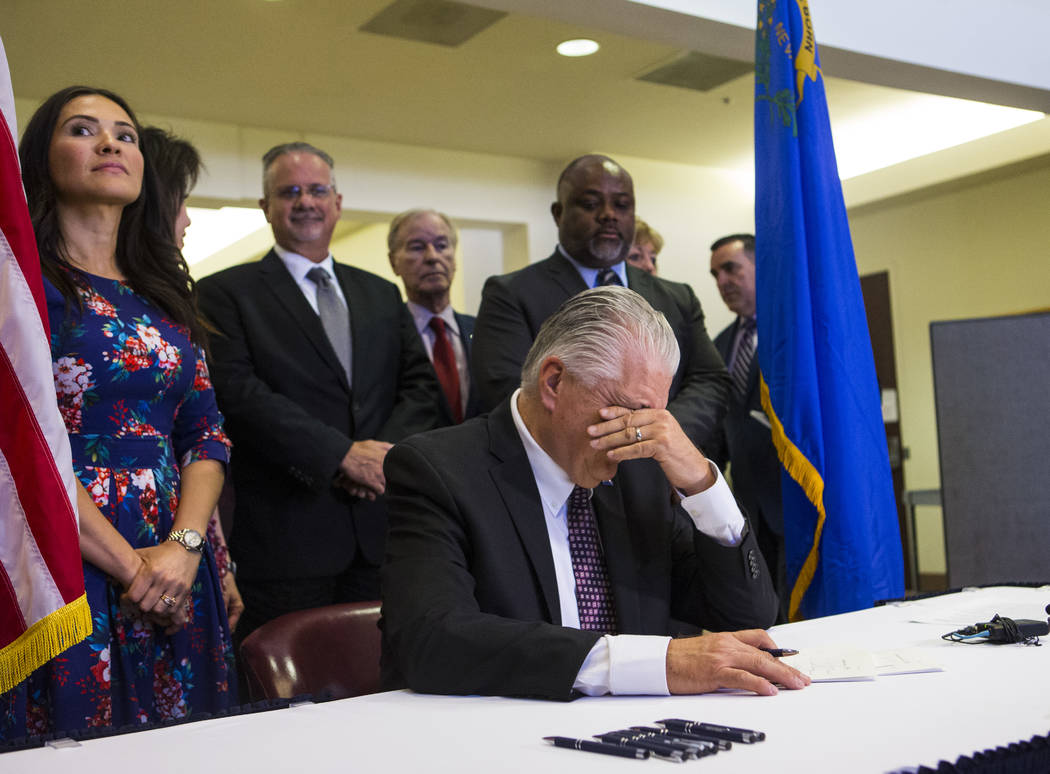 Gov. Steve Sisolak pauses for a moment before signing a trio of bills, including AB291, which i ...