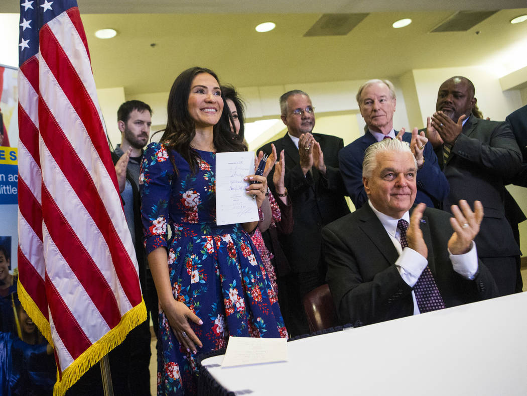 Gov. Steve Sisolak, right, claps after signing bill AB291, which includes a variety of gun cont ...