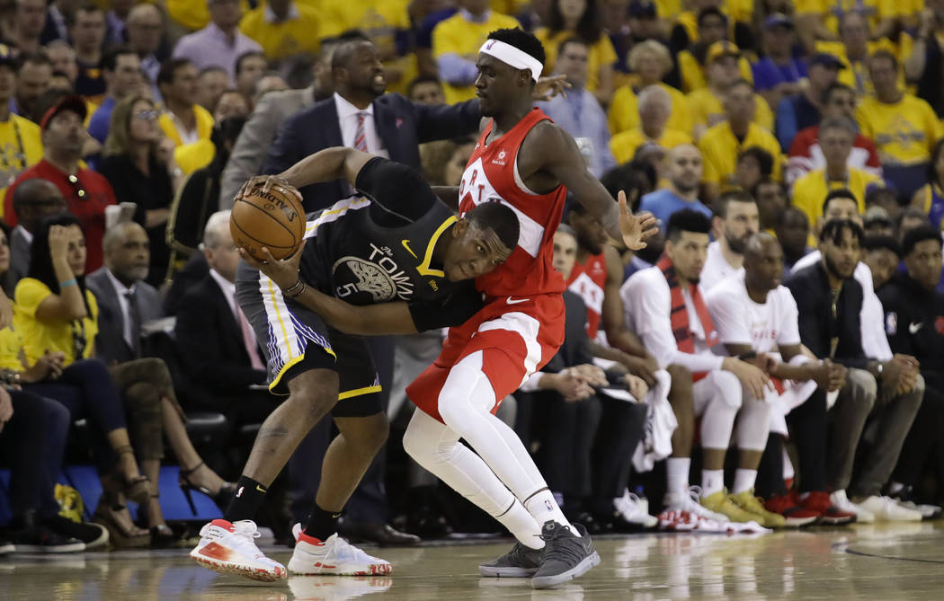 Golden State Warriors center Kevon Looney (5) is defended by Toronto Raptors forward Pascal Sia ...