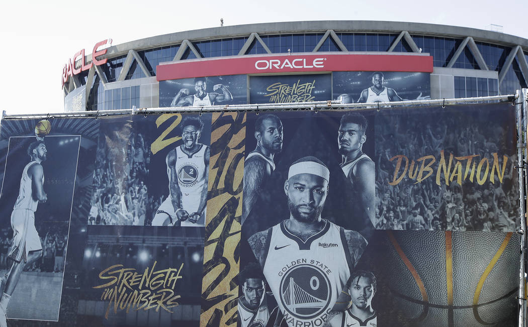 A sign showing images of Golden State Warriors players is displayed outside of Oracle Arena bef ...