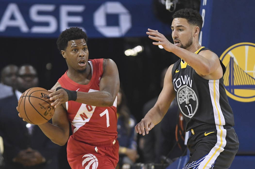 Toronto Raptors guard Kyle Lowry (7) passes the ball in front of Golden State Warriors guard Kl ...
