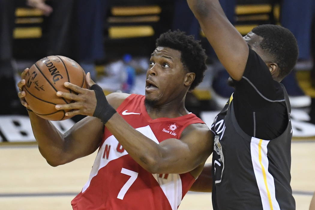 Toronto Raptors guard Kyle Lowry (7) gets off a shot in front of Golden State Warriors centre K ...