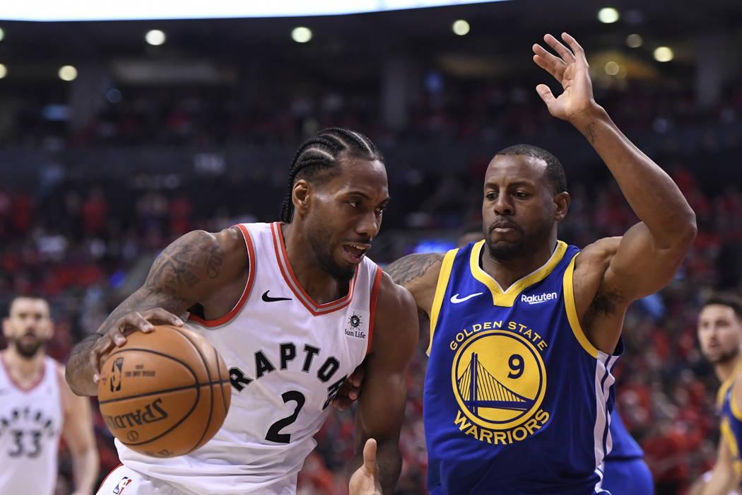 Toronto Raptors forward Kawhi Leonard (2) drives against Golden State Warriors forward Andre Ig ...