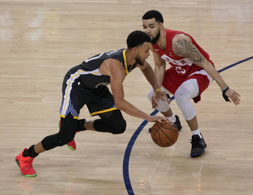 Golden State Warriors guard Stephen Curry, left, dribbles against Toronto Raptors guard Fred Va ...