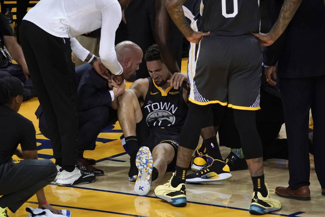 Golden State Warriors guard Klay Thompson, center, is helped up after being injured during the ...