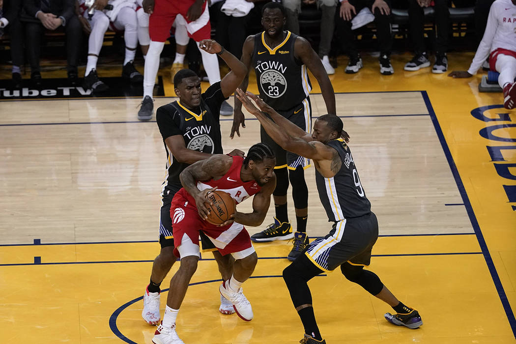 Toronto Raptors forward Kawhi Leonard, middle, is defended by Golden State Warriors center Kevo ...
