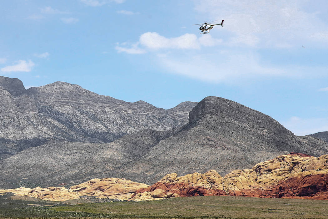 A helicopter flies near the Red Rock Overlook on U.S. Highway 159 in Red Rock Canyon National C ...